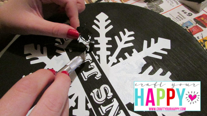 Using an exacto knife to remove pieces of the stencil film.