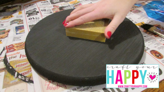 Sanding the painted wood round with a sanding sponge.
